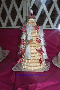 Kransekake or Crown Cake, is Norway's most famous cake. It consists of concentric rings of almond paste dough decorated with Norwegian flags and drizzled with vanilla cream icing.